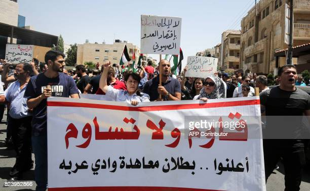 Jordanian protesters hold a banner reading in Arabic 'resist and do not compromise declare the annulment of the Wadi Arabah [peace] treaty' during a...