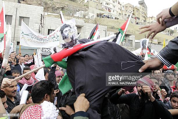 Jordanian protesters tear a dummy representing the leader of the Islamic State jihadist group Abu Bakr alBaghdadi during a demonstration on February...