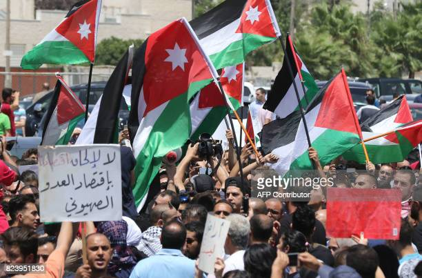 Jordanian protesters wave national flags and chant slogans during a demonstration near the Israeli embassy in the capital Amman on July 28 calling...
