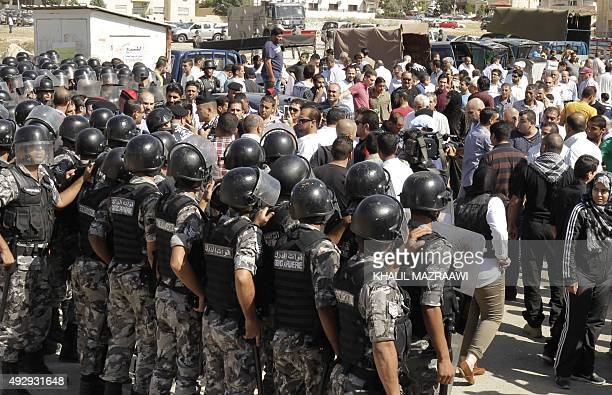 Jordanian riot police stand guard as protesters gather during a demonstration near the Israeli Embassy in the capital Amman in solidarity with the...