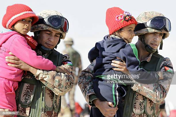 TOPSHOT Jordanian security forces help Syrian girls after crossing from Syria into Jordan at the Hadalat border crossing east of the Jordanian...