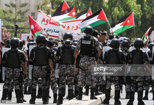 Jordanian security forces stand on guard before protesters as they wave national flags and chant slogans during a demonstration near the Israeli...