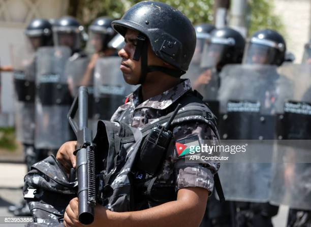 Jordanian security forces stand on guard before protesters during a demonstration near the Israeli embassy in the capital Amman on July 28 calling...