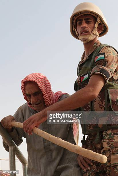 A Jordanian soldier helps an elderly Syrian refugee at the alRoqban makeshift camp on the border with Syria before driving a group of refugees to the...