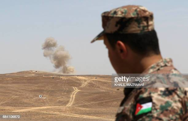 A Jordanian soldier looks on as smoke billows during the annual military exercises known as 'Eager Lion' near Maan some 200 kilometres south of the...