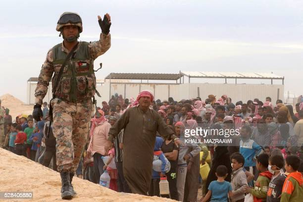 A Jordanian soldier stands guard as Syrian refugees arrive to a camp on the Jordanian side at the north east of Jordan's border with Syria at the...
