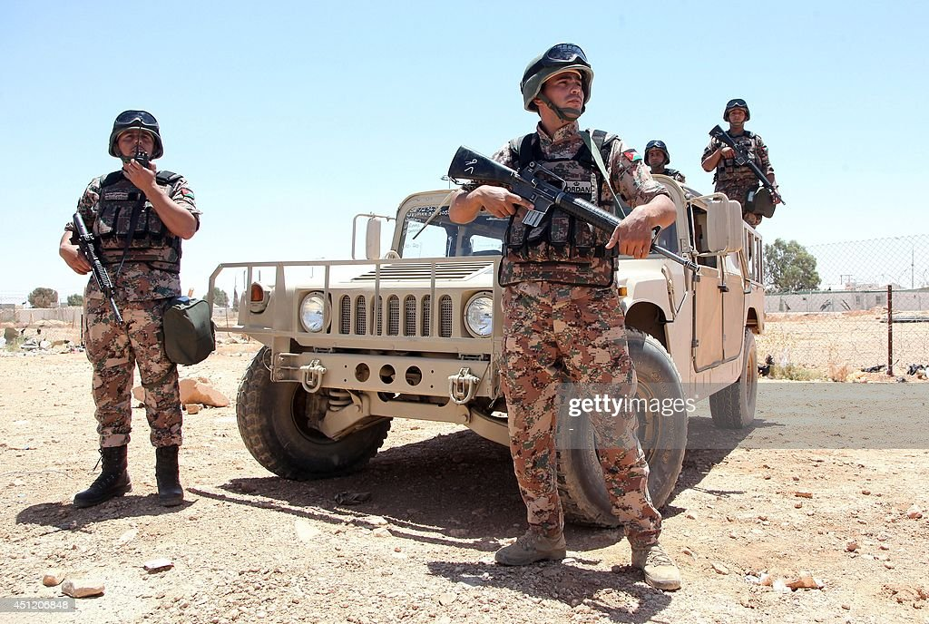 Jordanian soldiers stand guard near their vehicle as they secure the area near the AlKarameh border point with Iraq on June 25 2014 as Jordan...