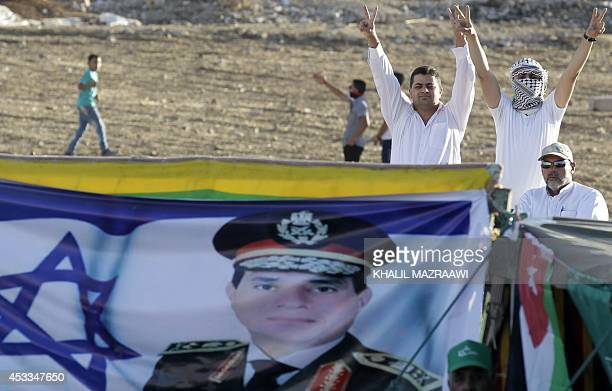 Jordanian supporters of the Muslim Brotherhood flash the VSign as they stand next to an Israeli flag bearing a portrait of Egyptian President Abdel...
