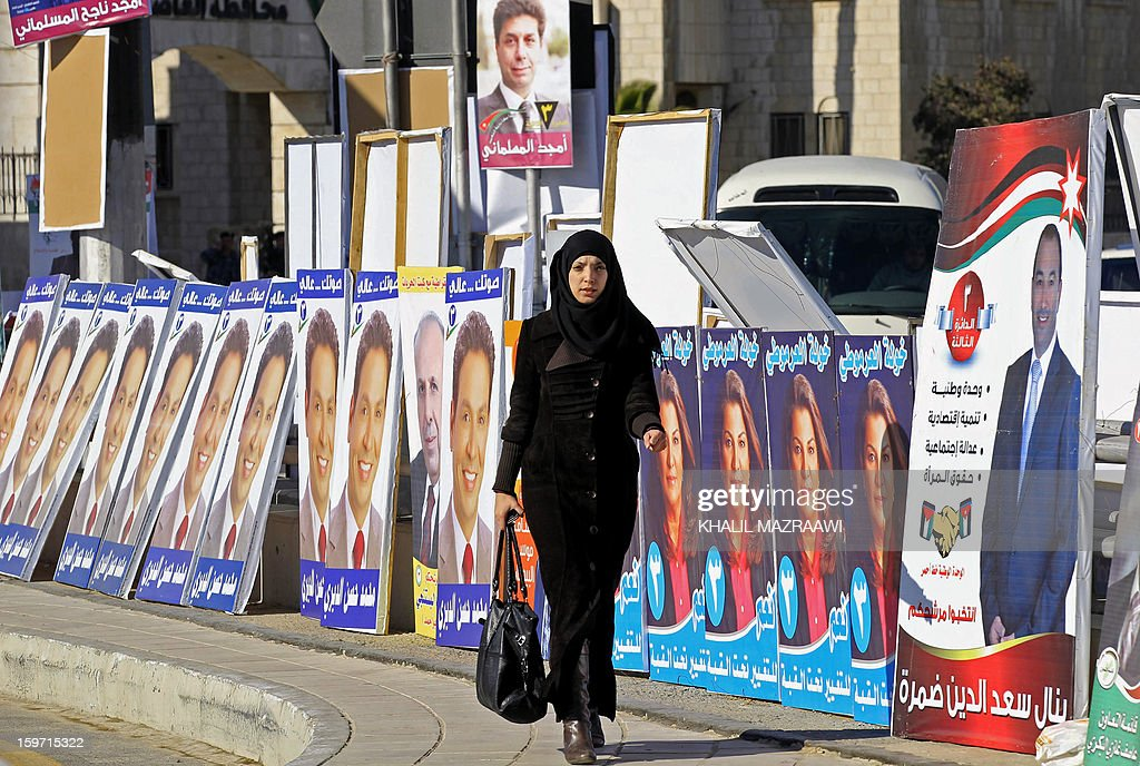A Jordanian woman walks past campaign posters of candidates for the Jordanian parliamentary elections in Amman on January 19, 2013. More than 1,500 candidates, including 213 women, have been registered for the January 23 election, which the opposition Islamists and other groups have boycotted over a lack of reform.