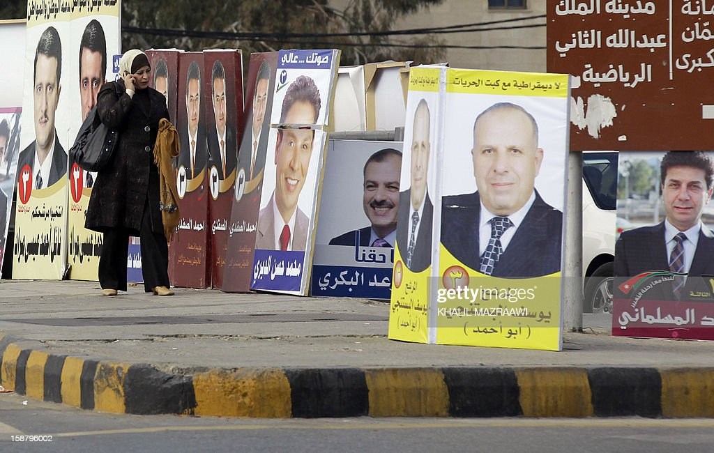 A Jordanian woman walks past pictures of parliament candidates in Amman on December 29, 2012. Jordan's electoral authority set January 23 as the date for a general election after King Abdullah II dissolved parliament despite a boycott pledge by the opposition Muslim Brotherhood.