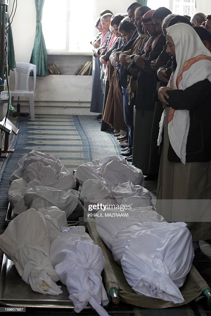 Jordanians and Syrians pray in front of the bodies of the Syrian refugees who were killed the day before during an explosion during their funeral in the northern city of Ramtha, which houses hundreds of refugees, on January 17, 2013. Eight Syrian refugees were killed when a kerosene heater exploded and the caravan in which they were living caught fire, and another four were hurt in the incident. AFP PHOTO KHALIL MAZRAAWI