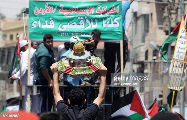 Jordanians carry a model of the Dome of the Rock mosque during a demonstration called for by the Islamic Action Front in Amman following friday...