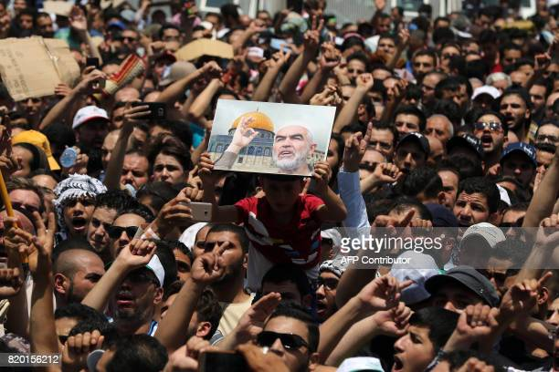 Jordanians carry a portrait of ArabIsraeli Sheikh Raed Salah the leader of the radical northern wing of the Islamic Movement in Israel as they shout...