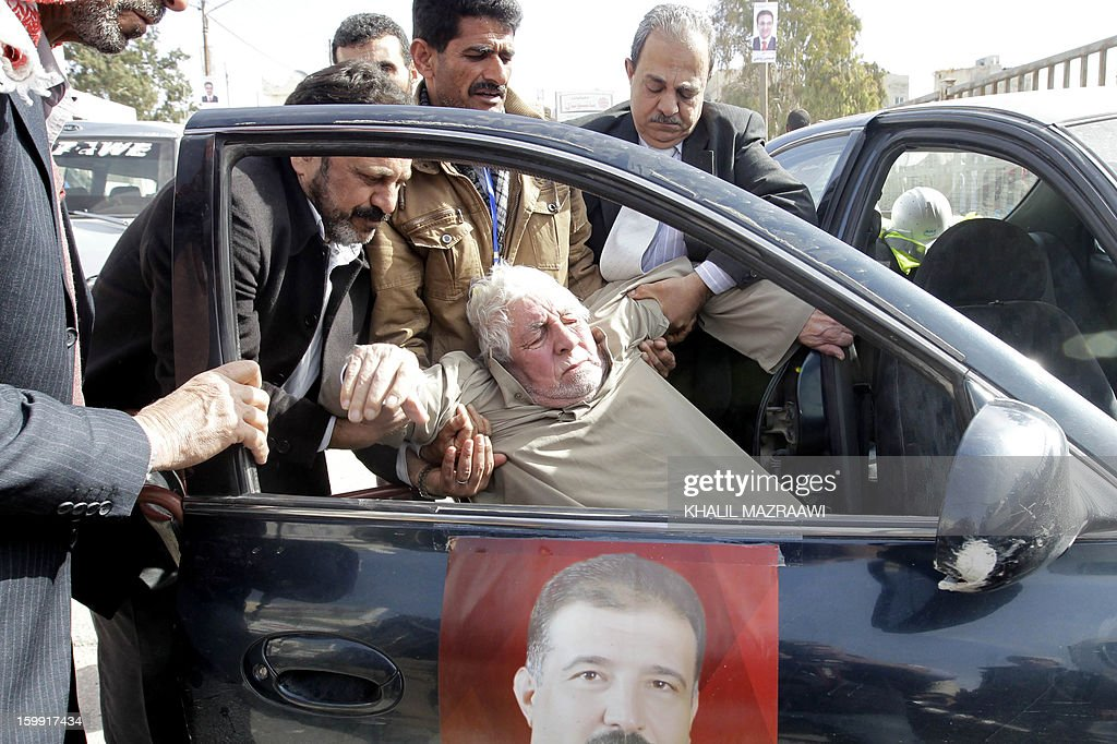 Jordanians carry an elderly man out of a car as he arrives to vote at a polling station in the Palestinian refugee camp of Baqaa, north of Amman, on January 23, 2013. Jordanians are voting in a parliamentary poll snubbed by Islamists who have staged strident pro-reform protests and who have already slammed what is expected to be an opposition-free body as illegitimate.