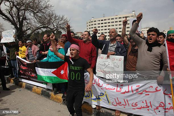 Jordanians shout slogans and hold signs in front of the Jordanian Parliament in Amman Jordan on March 18 2014 during a protest against Israel...