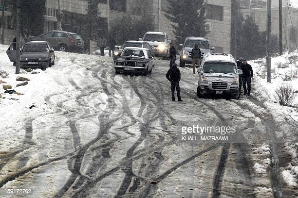 Jordanians stand by their cars as snow falls over Amman on January 9 2013 Extreme weather including torrential rains and heavy winds killed four...