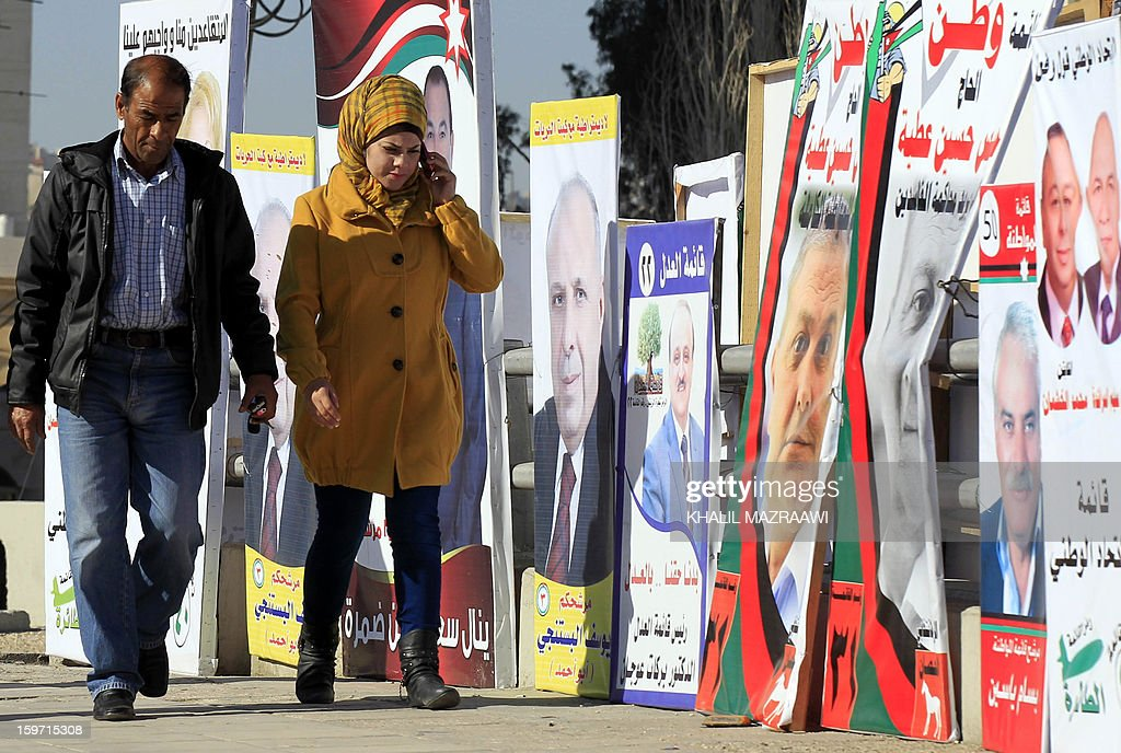 Jordanians walk past campaign posters of candidates for the Jordanian parliamentary elections in Amman on January 19, 2013. More than 1,500 candidates, including 213 women, have been registered for the January 23 election, which the opposition Islamists and other groups have boycotted over a lack of reform.