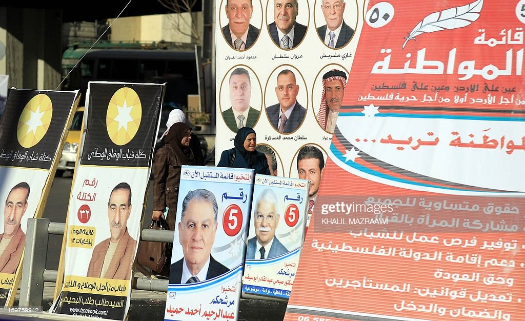 Jordanians walk past electoral campaign posters in Amman on January 19, 2013. Jordanians go to the polls on January 23, but an Islamist boycott is expected to produce a toothless parliament that is unlikely to bring real reform, leaving the country in political uncertainty.