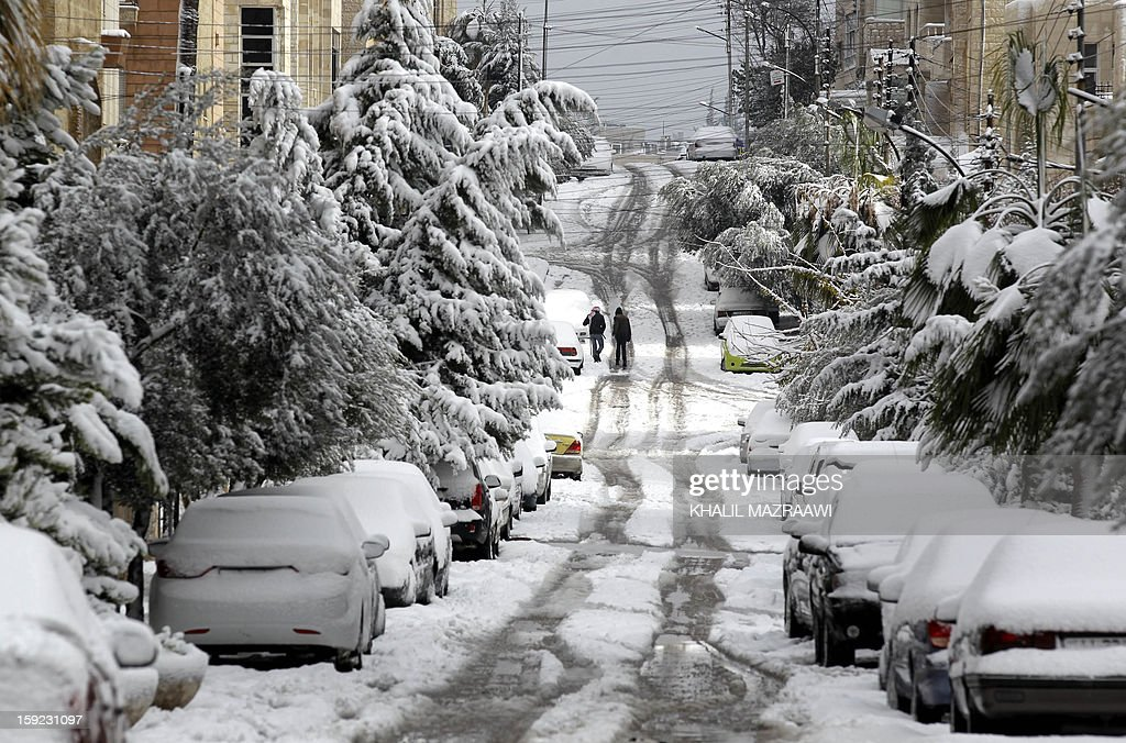 Jordanians walk past snow-covered cars and trees in Amman on January 10, 2013. The worst storms in a decade left swathes of Israel and Jordan under a blanket of snow and parts of Lebanon blacked out, bringing misery to a region accustomed to temperate climates. AFP PHOTO/KHALIL MAZRAAWI