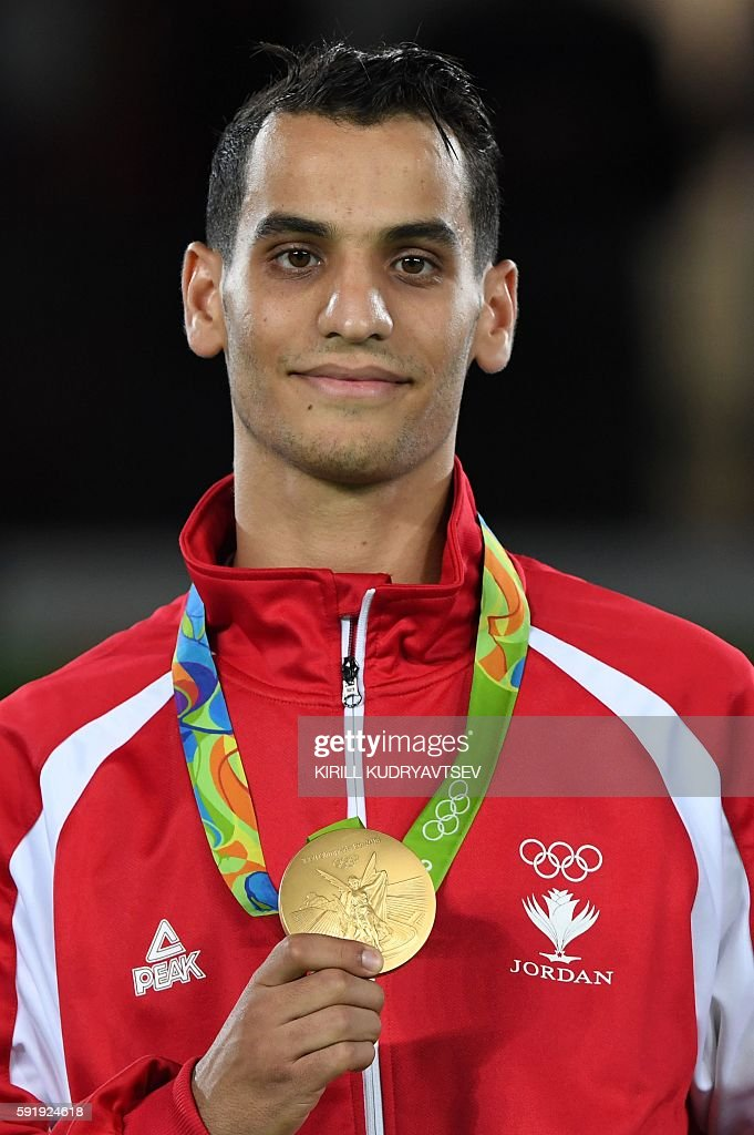 Jordan's Ahmad Abughaush poses with his gold medal on the podium after the men's taekwondo event in the -68kg category as part of the Rio 2016 Olympic Games, on August 18, 2016, at the Carioca Arena 3, in Rio de Janeiro. / AFP / Kirill KUDRYAVTSEV