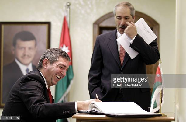 Jordan's Foreign Minister Nasser Judeh looks at his Greek counterpart Stavros Lambrinidis as he signs the guest book during a meeting at the Ministry...