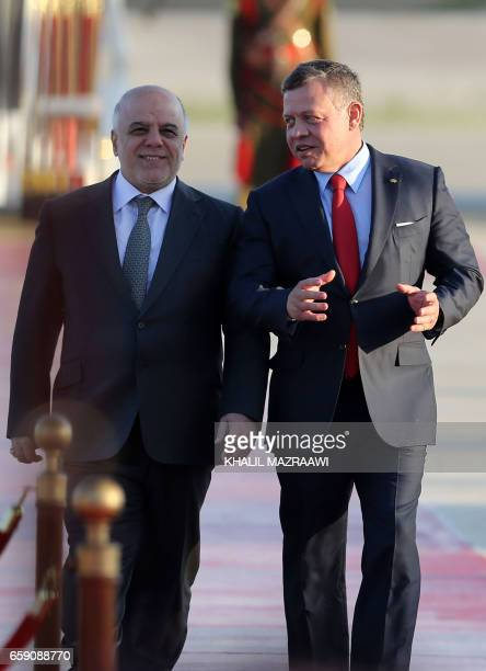 Jordan's King Abdullah II and Iraqi Prime Minister Haider alAbadi attend a welcome ceremony at the Queen Alia International Airport in Amman on March...