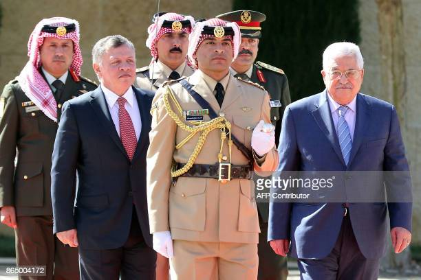 Jordan's King Abdullah II and Palestinian leader Mahmud Abbas review the honour guard upon the latter's arrival at the Royal Palace in Amman on...