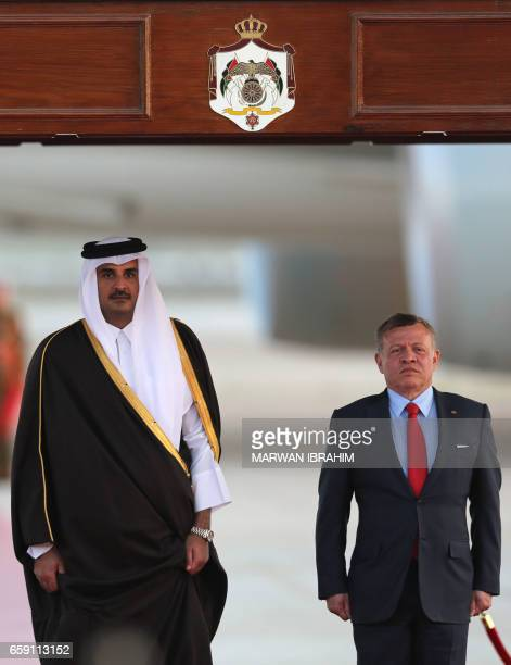 CORRECTION Jordan's King Abdullah II and Qatar's Emir Sheikh Tamim bin Hamad alThani attend a welcome ceremony at the Queen Alia International...