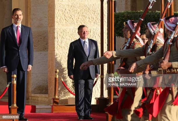 Jordan's King Abdullah II and Spain's King Felipe VI review the honour guard during a welcome ceremony in the capital Amman on May 19 2017 / AFP...