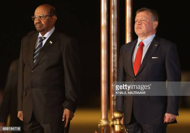 Jordan's King Abdullah II and Sudanese President Omar alBashir attend a welcome ceremony at the Queen Alia International Airport in Amman on March 28...