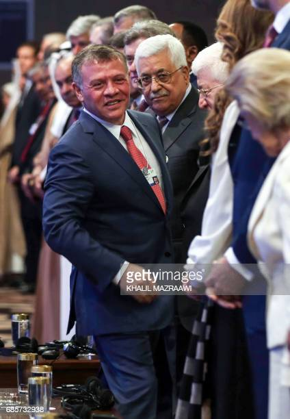 Jordan's King Abdullah II reaches out to shake hands with King Felipe VI of Spain during the opening session of the World Economic Forum held in the...
