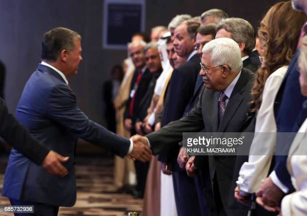 Jordan's King Abdullah II shakes hands with Palestinian president Mahmud Abbas during the opening session of the World Economic Forum held in the...