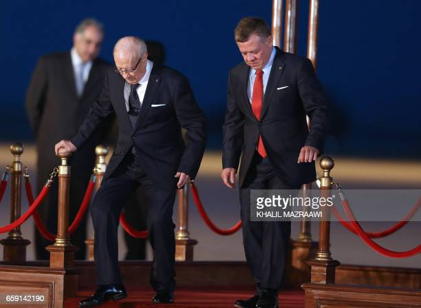 Jordan's King Abdullah II Tunisian President Beji Caid Essebsi attend a welcome ceremony at the Queen Alia International Airport in Amman on March 28...