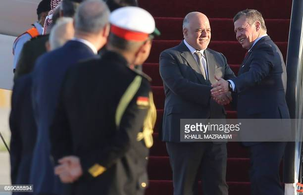 Jordan's King Abdullah II welcomes Iraqi Prime Minister Haider alAbadi during a welcome ceremony at the Queen Alia International Airport in Amman on...