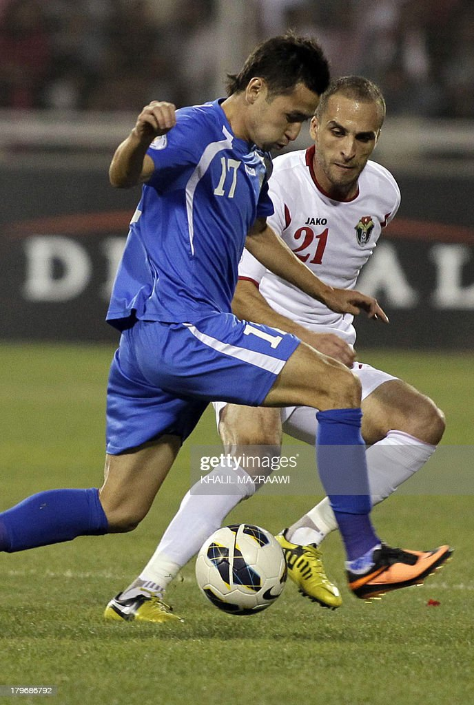 Jordan's Mohammed al-Dumeiri (R) challenges Uzbekistan's Sanjar Tursunov for the ball during their 2014 World Cup qualifier football match at the King Abdullah international stadium in Amman on September 6, 2012. The match ended in a draw.