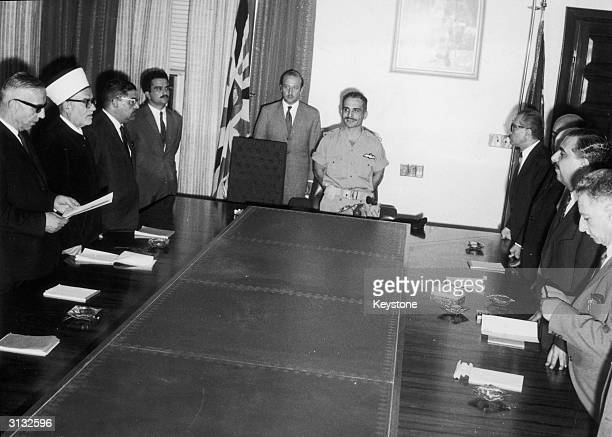 Jordan's new cabinet takes the constitutional oath before King Hussein at the Royal Court in Amman 1st July 1970 To the king's left in glasses is new...