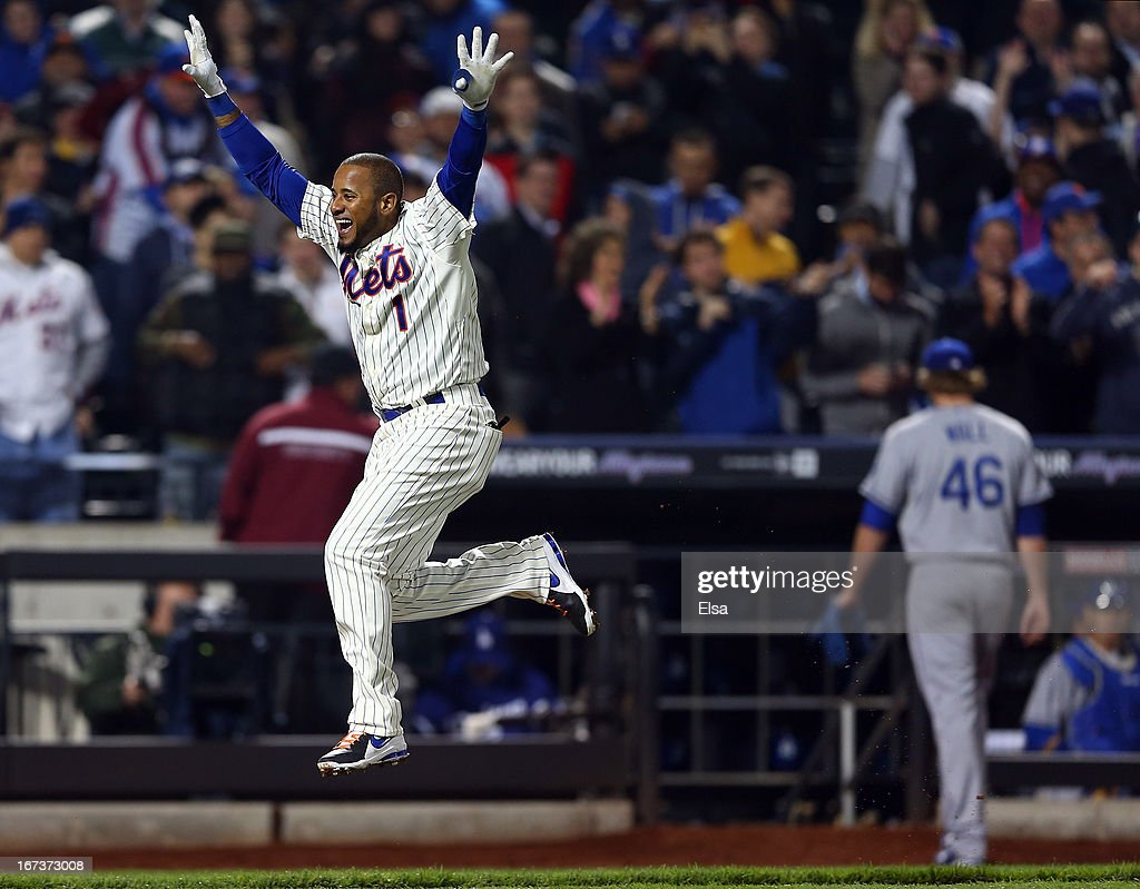 Jordany Valdespin #1 of the New York Mets celebrates his game winning grand slam as Josh Wall #46 of the Los Angeles Dodgers walks off the field on April 24, 2013 at Citi Field in the Flushing neighborhood of the Queens borough of New York City. The New York Mets defeated the Los Angeles Dodgers 7-3 in 10 innings.