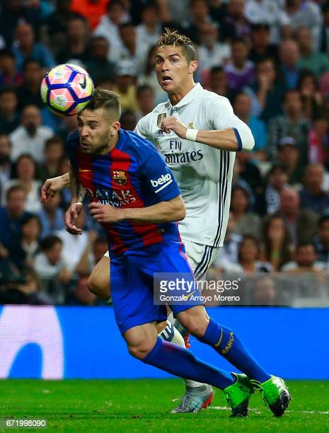 Jordi Alba of Barcelona heads the ball clear as Cristiano Ronaldo of Real Madrid closes in during the La Liga match between Real Madrid CF and FC...