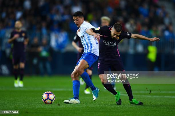 Jordi Alba of FC Barcelona competes for the ball with Pablo Fornals of Malaga CF during the La Liga match between Malaga CF and FC Barcelona at La...