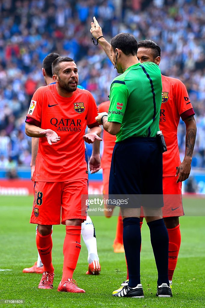 Jordi Alba (L) of FC Barcelona is shown a red card by the referee Antonio Miguel Mateu Lahoz during the La Liga match between RCD Espanyol and FC Barcelona at Cornella-El Prat Stadium on April 25, 2015 in Barcelona, Spain.