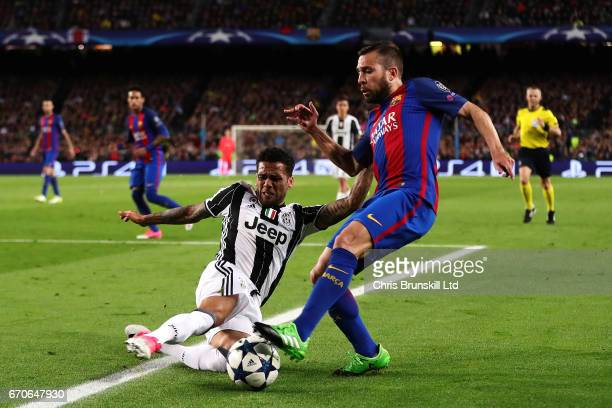 Jordi Alba of FC Barcelona is tackled by Dani Alves of Juventus during the UEFA Champions League Quarter Final second leg match between FC Barcelona...
