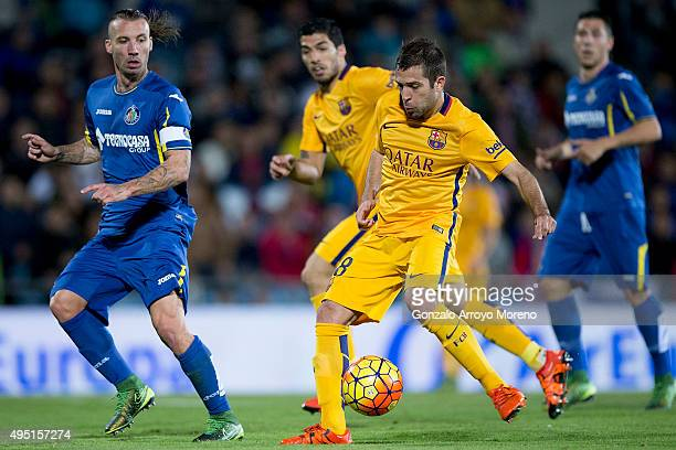 Jordi Alba of FC Barcelona strikes the ball ahead Alexis Ruano of Getafe CF during the La Liga match between Getafe CF and FC Barcelona at Coliseum...