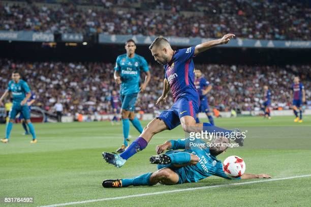 Jordi Alba of FC Barcelona trips up with Daniel Carvajal of Real Madrid during the Supercopa de Espana Final 1st Leg match between FC Barcelona and...