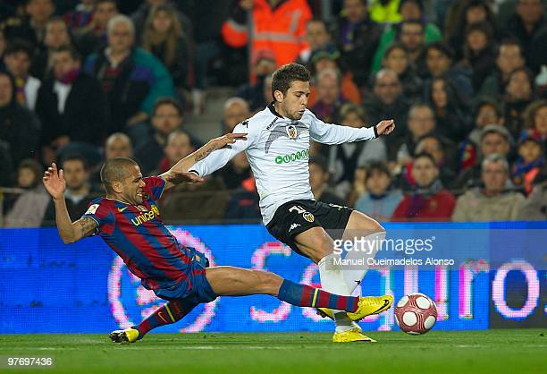 Jordi Alba of Valencia is tackled by Dani Alves of Barcelona during the La Liga match between and Valencia at the Camp Nou Stadium on March 14 2010...