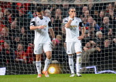 Jordi Amat and Chico Flores of Swansea City react after conceding a second goal during the Barclays Premier League match between Manchester United...