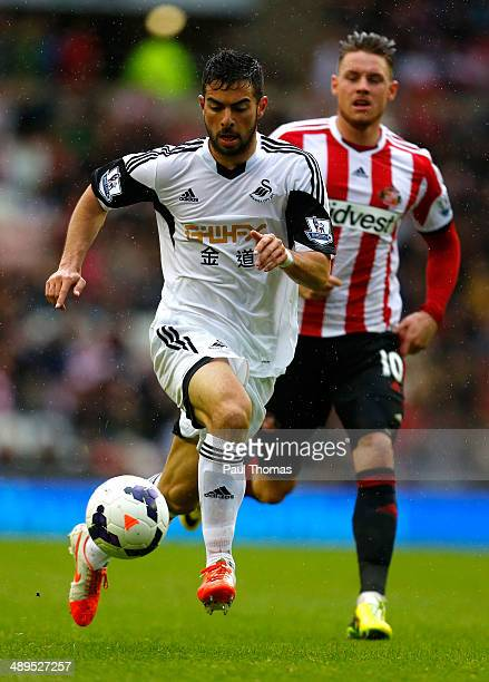 Jordi Amat of Swansea City is chased by Connor Wickham of Sunderland during the Barclays Premier League match between Sunderland and Swansea City at...