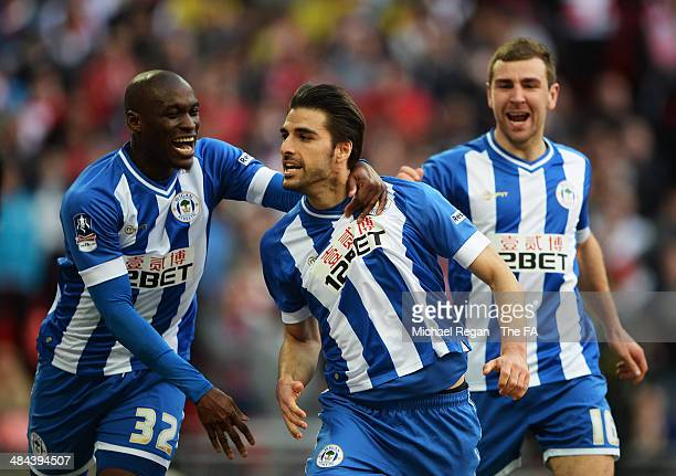 Jordi Gomez of Wigan Athletic celebrates with teammates James McArthur and MarcAntoine Fortune after scoring a goal from the penalty spot during the...