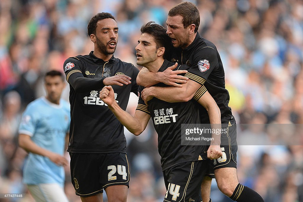<a gi-track='captionPersonalityLinkClicked' href=/galleries/search?phrase=Jordi+Gomez&family=editorial&specificpeople=1323748 ng-click='$event.stopPropagation()'>Jordi Gomez</a> of Wigan celebrates scoring a penalty to make it 1-0 with team mates James McArthur and <a gi-track='captionPersonalityLinkClicked' href=/galleries/search?phrase=James+Perch&family=editorial&specificpeople=2211397 ng-click='$event.stopPropagation()'>James Perch</a> during the FA Cup Quarter-Final match between Manchester City and Wigan Athletic at the Etihad Stadium on March 9, 2014 in Manchester, England.
