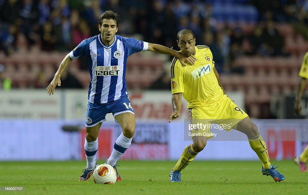 Jordi Gomez of Wigan holds off Tavares of NK Maribor during the UEFA Europa League match between Wigan and NK Maribor at DW Stadium on October 3, 2013 in Wigan, England.