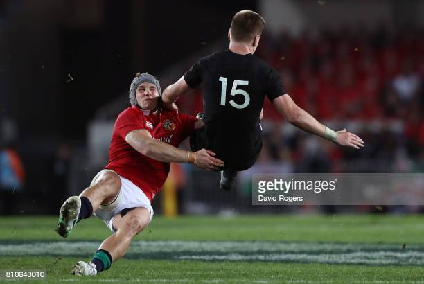 Jordie Barrett of the All Blacks is tackled by Jonathan Davies of the Lions as he attempts to clear the ball during the third test match between the...